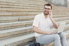 Jeune homme d'affaires gai utilisant l'ordinateur portable et faire un appel sur le sta photographie stock