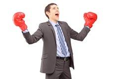 Jeune homme d'affaires heureux dans le costume avec faire des gestes rouge de gants de boxe Images stock