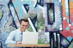 jeune homme d'affaires heureux dans les écouteurs et des lunettes utilisant le moment d'ordinateur portable photos libres de droits