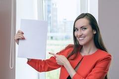Jeune homme d'affaires heureux dans un costume rouge, tenant une feuille blanche vide pour le texte sur le fond des portes en boi Photo stock