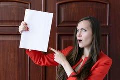 Jeune homme d'affaires heureux dans un costume rouge, tenant une feuille blanche vide pour le texte sur le fond des portes en boi Images libres de droits