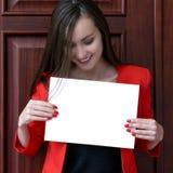 Jeune homme d'affaires heureux dans un costume rouge, tenant une feuille blanche vide pour le texte sur le fond des portes en boi Image stock