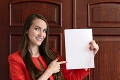 Jeune homme d'affaires heureux dans un costume rouge, tenant une feuille blanche vide pour le texte sur le fond des portes en boi Photos libres de droits