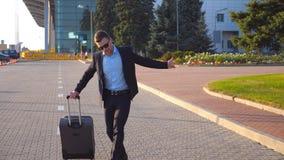 Jeune homme d'affaires heureux dans une danse drôle et un chant de costume noir formel tout en allant avec le bagage sur la rue d clips vidéos