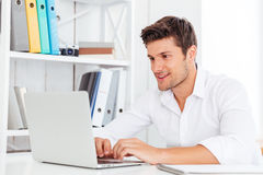 Jeune homme d'affaires heureux de sourire utilisant l'ordinateur portable Photographie stock