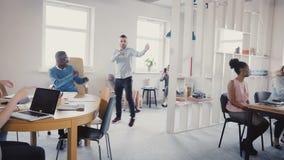 Jeune homme d'affaires heureux faisant la danse de victoire, célébrant le succès d'équipe avec des employés de métis dans le bure banque de vidéos