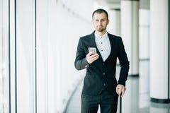 Jeune homme d'affaires heureux marchant et regardant le téléphone portable l'aéroport Service de mini-messages beau de cadre comm photos libres de droits
