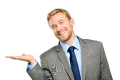 Jeune homme d'affaires heureux montrant le copyspace vide sur le blanc Image libre de droits