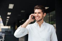 Jeune homme d'affaires heureux parlant au téléphone portable près du centre d'affaires image stock