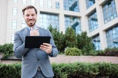 Jeune homme d'affaires heureux travaillant à un comprimé devant un immeuble de bureaux photos libres de droits