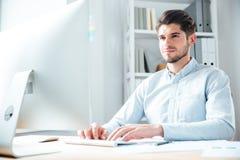 Jeune homme d'affaires heureux utilisant l'ordinateur portable dans le bureau Photos libres de droits