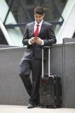 Jeune homme d'affaires indien avec le sac de bagage utilisant le téléphone portable images libres de droits