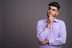Jeune homme d'affaires indien bel sur le fond gris photo stock
