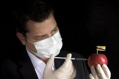 Jeune homme d'affaires injectant des produits chimiques dans une pomme avec le Brunei image stock