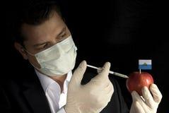 Jeune homme d'affaires injectant des produits chimiques dans une pomme avec San mars Photos libres de droits