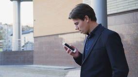 Jeune homme d'affaires inquiété faisant un appel sur le smartphone au bureau 4K banque de vidéos