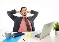 Jeune homme d'affaires latin attirant dans le costume et lien fonctionnant au bureau d'ordinateur de bureau se penchant de retour Photographie stock libre de droits