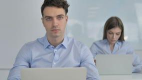 Jeune homme d'affaires Looking à la caméra dans le bureau clips vidéos