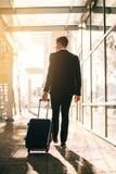 Jeune homme d'affaires marchant avec la valise à l'extérieur du bâtiment d'aéroport Photos libres de droits