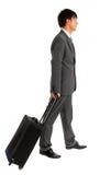 Jeune homme d'affaires marchant avec sa valise de chariot Images libres de droits