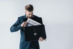 Jeune homme d'affaires mettant le journal dans la serviette photographie stock libre de droits