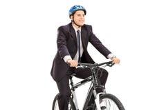 Jeune homme d'affaires montant une bicyclette Photos stock