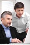 Jeune homme d'affaires montrant à son patron quelque chose sur l'ordinateur portable. Photos libres de droits