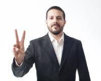 Jeune homme d'affaires montrant le signe de paix Photos stock