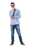Jeune homme d'affaires occasionnel futé pensant avec des mains sur les lunettes de soleil de port de menton Image stock