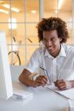 Jeune homme d'affaires occasionnel s'asseyant à son bureau souriant à l'ordinateur Photo libre de droits