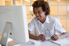 Jeune homme d'affaires occasionnel s'asseyant à son bureau souriant à l'ordinateur Photographie stock libre de droits