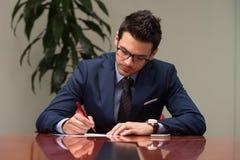 Jeune homme d'affaires In Office Looking au papier Photographie stock libre de droits