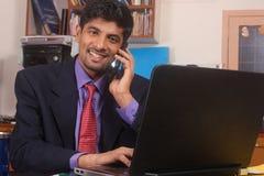 Jeune homme d'affaires parlant au téléphone portable dans le bureau Photo libre de droits