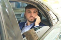 Jeune homme d'affaires parlant par le téléphone sur le siège arrière de la voiture Image libre de droits