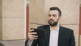 Jeune homme d'affaires parlant sur la tablette ayant la causerie visuelle avec son épouse Homme d'affaires employant l'APP pour a banque de vidéos