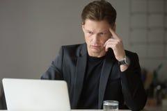 Jeune homme d'affaires perplexe regardant l'écran d'ordinateur portable le workplac Images libres de droits