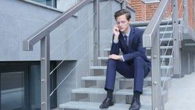 Jeune homme d'affaires Phone Talk, négociation, se reposant sur des escaliers en dehors de bureau banque de vidéos