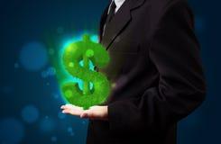 Jeune homme d'affaires présent le symbole dollar rougeoyant vert Photo stock