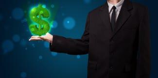 Jeune homme d'affaires présent le symbole dollar rougeoyant vert Photos libres de droits
