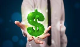 Jeune homme d'affaires présent le symbole dollar rougeoyant vert Images stock