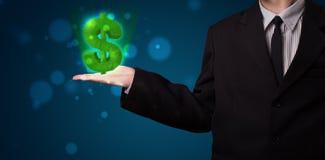 Jeune homme d'affaires présent le symbole dollar rougeoyant vert Image stock