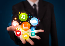 Jeune homme d'affaires présent les icônes colorées de technologie Images libres de droits