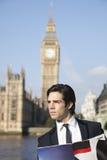 Jeune homme d'affaires réfléchi avec le livre contre la tour d'horloge de Big Ben, Londres, R-U Photos stock