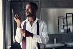 jeune homme d'affaires réfléchi dans la chemise blanche boutonnant des boutons de manchette image libre de droits