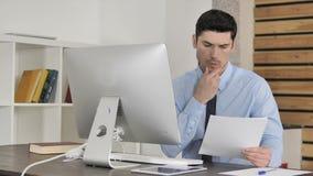 Jeune homme d'affaires réfléchi Reading Documents au travail, pensant banque de vidéos