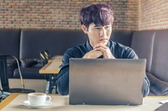 Jeune homme d'affaires réfléchi s'asseyant avec son ordinateur portable à un café, Photo stock