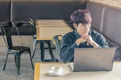 Jeune homme d'affaires réfléchi s'asseyant avec son ordinateur portable à un café Images libres de droits