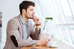 Jeune homme d'affaires réfléchi tenant le journal tout en ayant la pause-café images stock