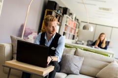Jeune homme d'affaires réussi dactylographiant sur l'ordinateur portable photo libre de droits