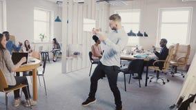 Jeune homme d'affaires réussi faisant la danse de victoire dans le bureau multi-ethnique léger moderne, les gens battant et riant banque de vidéos